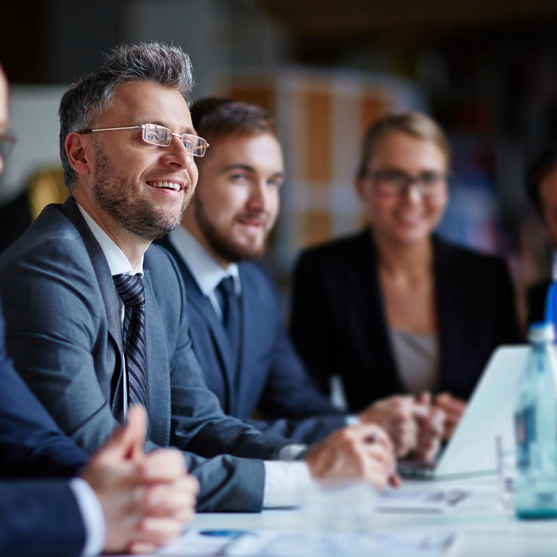 Group of smiling business people sitting together at a meeting